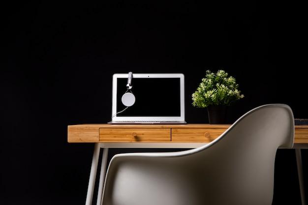 Mesa de madeira com cadeira e laptop Foto gratuita