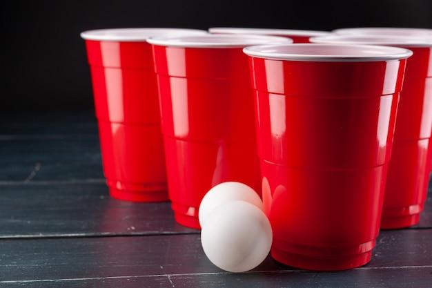 Mesa de madeira com copos vermelhos e bola para pong de cerveja Foto Premium