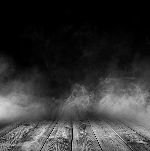 Mesa de madeira com fumaça e fundo preto Foto Premium