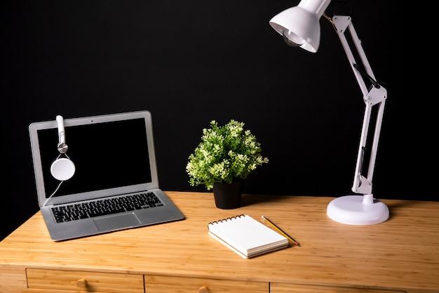 Mesa de madeira com lâmpada e laptop Foto gratuita