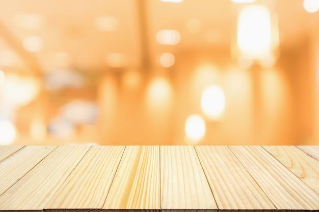 Mesa de madeira com restaurante café desfocado abstrato com luzes bokeh fundo desfocado Foto Premium