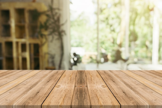 Mesa de madeira mesa vazia em frente ao fundo desfocado. perspectiva de madeira marrom sobre borrão na cafeteria - pode ser usado para exibir ou montar seus produtos. insira a exibição do produto. Foto gratuita