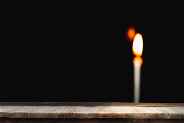 Mesa de madeira na frente da luz de borrão vela acesa brilhantemente em preto Foto Premium
