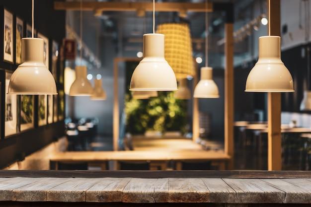 Mesa de madeira na frente de lâmpadas decorativas modernas Foto Premium