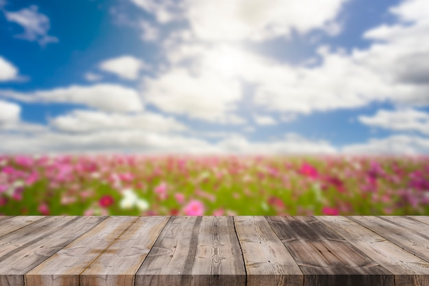 Mesa de madeira no borrão azul céu e cosmos flor fundo Foto Premium