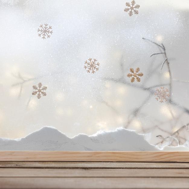 Mesa de madeira perto do banco de neve, flocos de neve e luzes de fada Foto gratuita