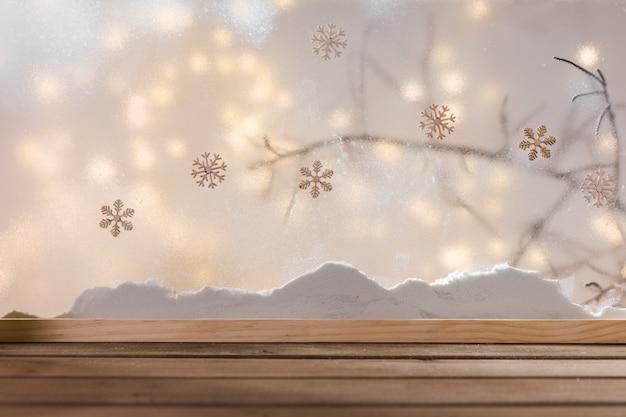 Mesa de madeira perto do banco de neve, galho de planta, flocos de neve e luzes de fada Foto gratuita