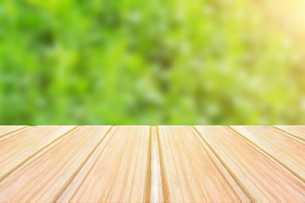 Mesa de madeira vazia com fundo verde turva. festa conceito, produtos, primavera Foto Premium