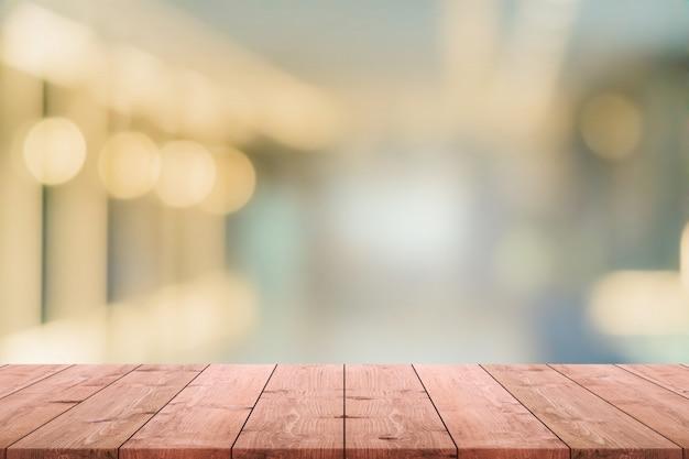 Mesa de madeira vazia e café turva e restaurent fundo interior - pode ser usado para exibir ou montagem de seus produtos. Foto Premium