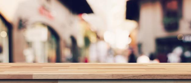Mesa de madeira vazia e mesa de luz turva em shopping com fundo de bokeh. modelo de exibição do produto. Foto Premium