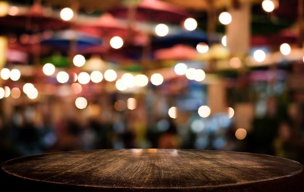 Mesa de madeira vazia na frente do abstrato turva luz de fundo festivo com manchas de luz e bokeh Foto Premium