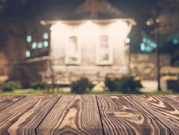 Mesa de madeira vazia na frente do pano de fundo da casa turva Foto gratuita