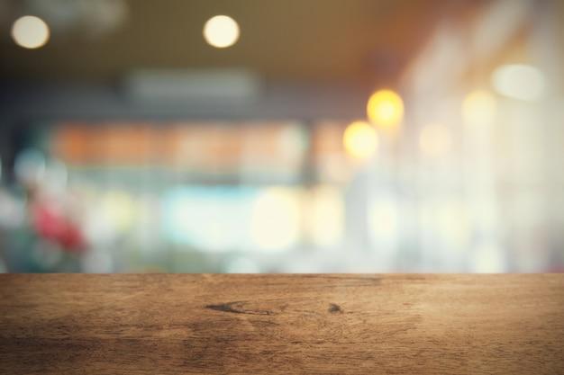 Mesa de madeira vazia no fundo da loja de café borrão Foto Premium