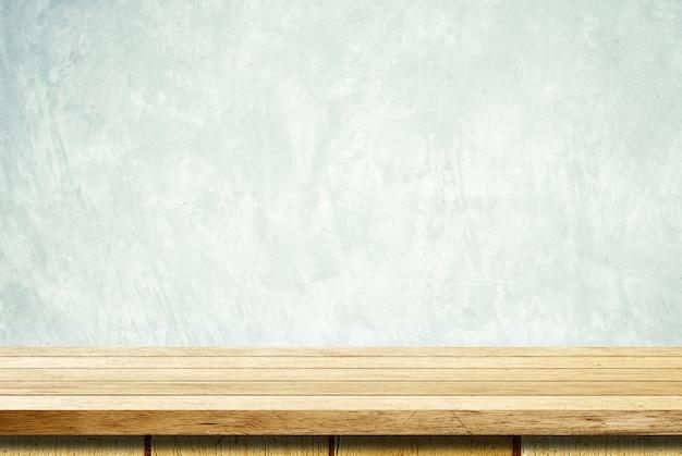 Mesa de madeira vazia sobre fundo de parede de cimento grunge Foto Premium
