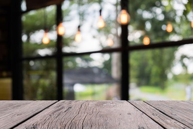 Mesa de madeira velha na frente com fundo desfocado restaurent, para objeto de persent Foto Premium