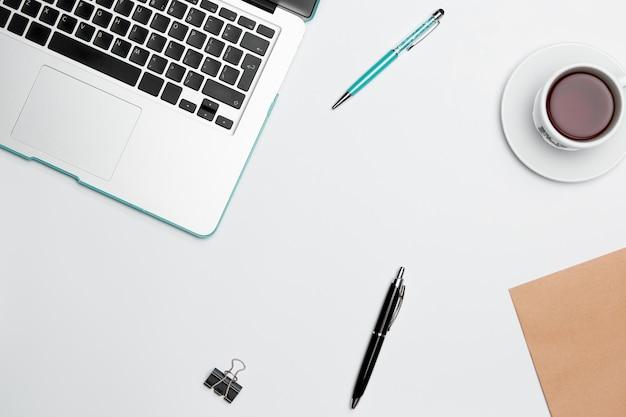 Mesa de mesa de escritório com computador, suprimentos, flores e xícara de café Foto gratuita