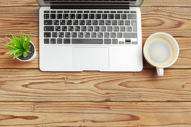 Mesa de mesa de escritório de madeira e equipamentos para trabalhar com café preto em vista de ângulo Foto Premium