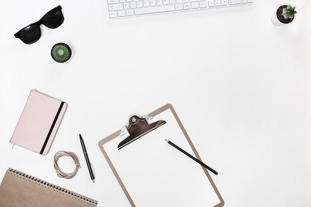 Mesa de mesa do blogueiro branco moderno com teclado branco, tablet pasta, cacto e diário-de-rosa Foto Premium