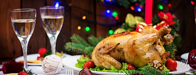 Mesa de natal servida com um peru, decorado com enfeites e velas brilhantes Foto Premium