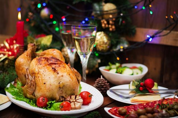 Mesa de natal servida com um peru, decorado com enfeites e velas brilhantes Foto gratuita