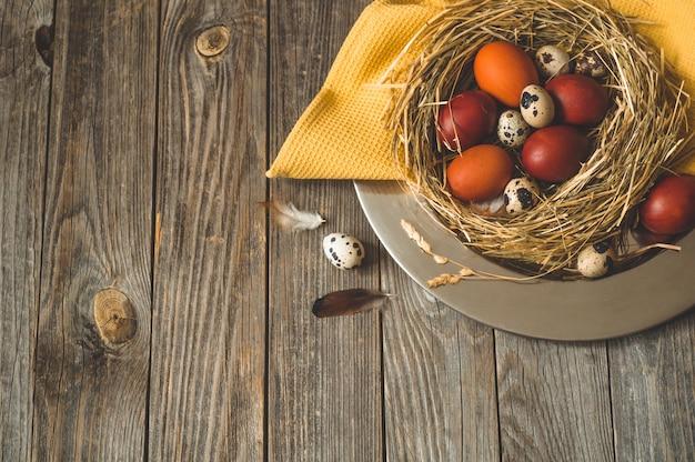 Mesa de páscoa feliz ovos de páscoa em um ninho em uma placa de metal em uma mesa de madeira. feliz páscoa conceito Foto gratuita