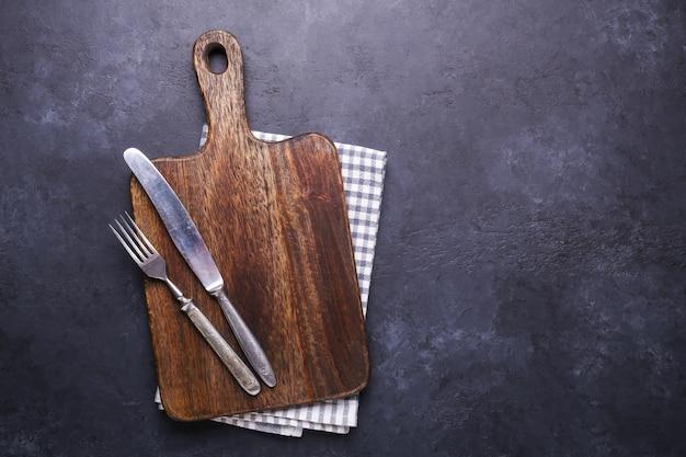 Mesa de pedra escura com placa de corte e guardanapo de linho garfo e faca vintage copie o espaço Foto Premium