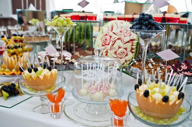 Mesa de sobremesa de deliciosos doces na recepção do casamento. Foto Premium
