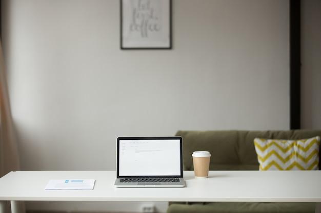 Mesa de trabalho com laptop, café e documentos no interior de casa Foto gratuita