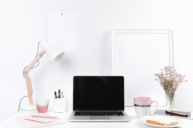 Mesa de trabalho com laptop e lanches Foto gratuita