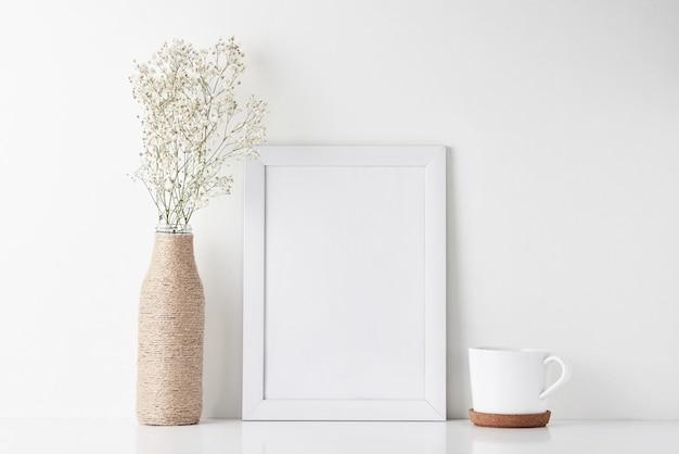 Mesa de trabalho com moldura vazia e flor em vaso Foto Premium