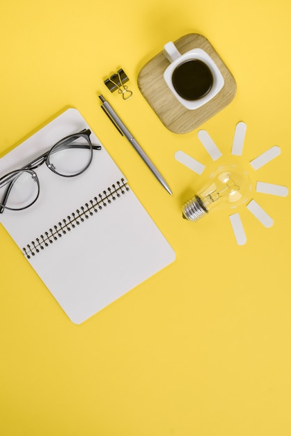 Mesa de trabalho design de estilo de material de escritório com caneta, bloco de notas, óculos, xícara de café e lâmpada Foto Premium