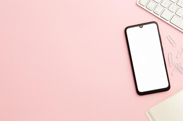 Mesa de trabalho mulher rosa com telefone e cópia de espaço Foto gratuita