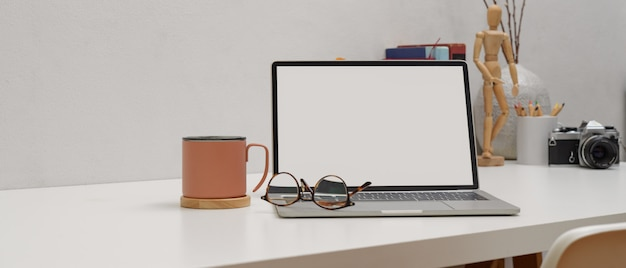 Mesa de trabalho simples com mock-se laptop, óculos, caneca e suprimentos na mesa branca com cadeira branca Foto Premium