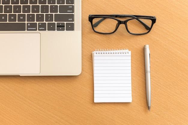 Mesa de vista superior com o bloco de notas e laptop na mesa de escritório de madeira Foto Premium