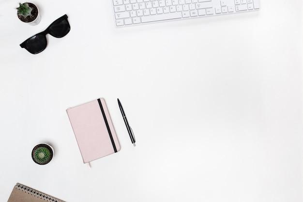 Mesa do blogger com teclado branco, smatphone, cacto e diário rosa Foto Premium