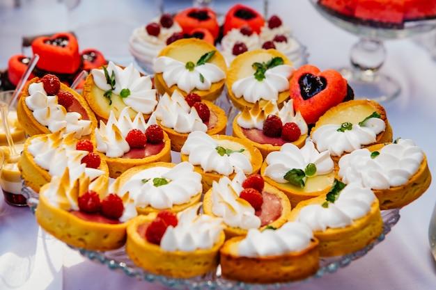 Mesa doce com bolos de frutas com creme e doçura. barra de chocolate deliciosa. serviço de barra de chocolate de casamento Foto Premium