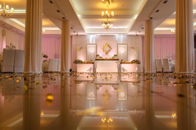 Mesa festiva decorada com composição de flores brancas, vermelhas e rosa e vegetação no salão de banquetes. Foto Premium