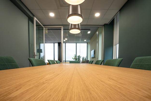 Mesa marrom cercada por cadeiras verdes sob lâmpadas em uma sala Foto gratuita