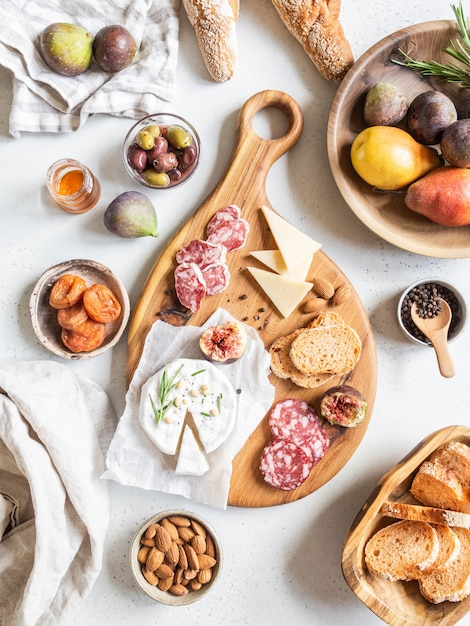 Mesa posta para lanches. variedade de queijo, azeitonas, salsichas, fatias de baguete, figos, nozes na placa de madeira, postura plana. vista do topo. Foto Premium