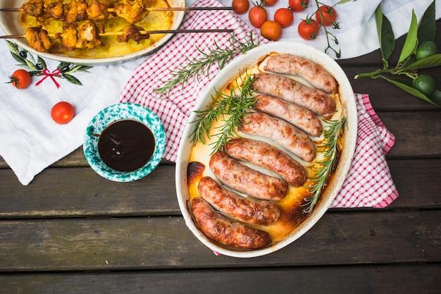 Mesa servida com carne grelhada e salsichas Foto gratuita