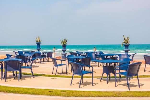 Mesa vazia e cadeira em torno do fundo da praia Foto gratuita