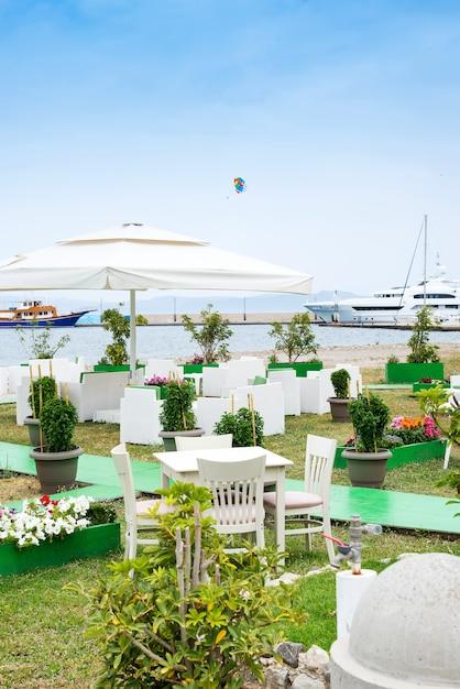 Mesas de café servidas com uma toalha de mesa branca perto da costa do mar para umas férias relaxantes Foto Premium