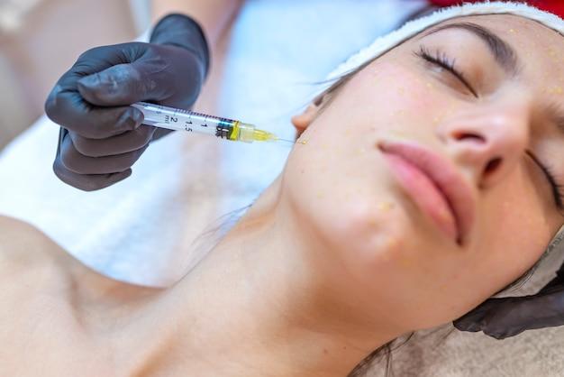 Mesoterapia na testa. tratamento mesoterapia. procedimento de mesoterapia. o cosmetologista médico faz o procedimento de mesoterapia na cabeça da mulher. fortalecer o cabelo e seu crescimento. Foto Premium