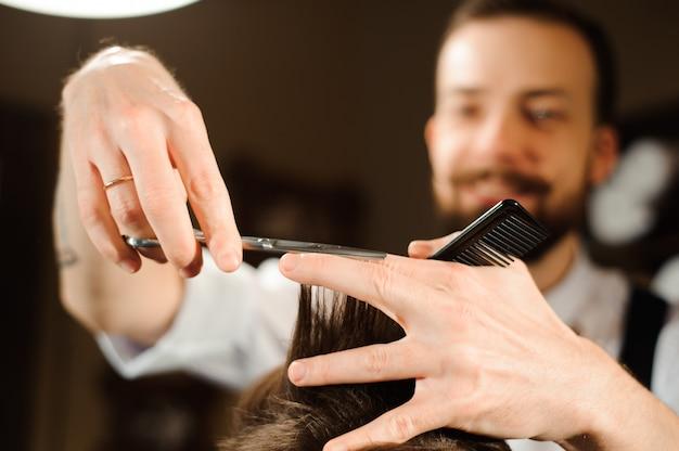 Mestre corta cabelo e barba de homens na barbearia Foto Premium