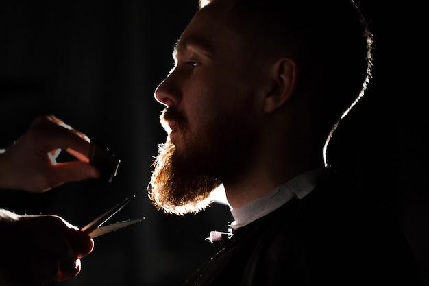 Mestre corta cabelo e barba na barbearia Foto Premium
