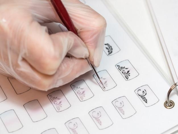 Mestre desenha um monograma. treinamento em monogramas de pintura para manicure Foto Premium