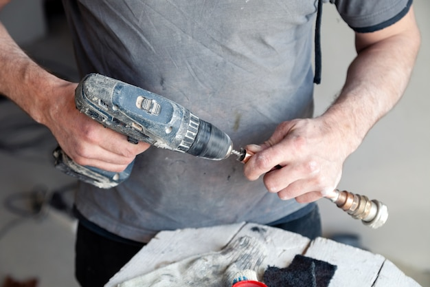 Mestre do encanador do trabalhador do close up que limpa as tubulações de cobre com a escova profissional. Foto Premium