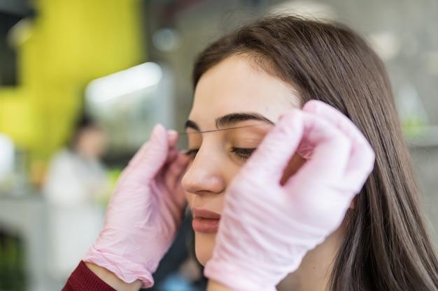 Mestre feminina em luvas brancas verifica o contorno das sobrancelhas Foto gratuita
