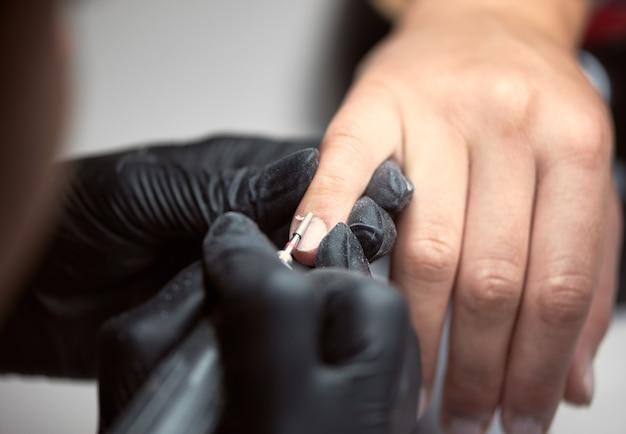 Mestre manicure profissional trabalhando nas unhas dos clientes Foto Premium