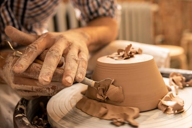 Mestre na arte da cerâmica, tornando as laterais da nova tigela de argila planas e lisas com uma ferramenta manual especial durante o trabalho Foto Premium
